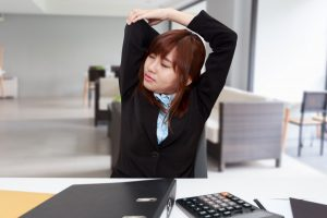 Office employee stretching at her desk